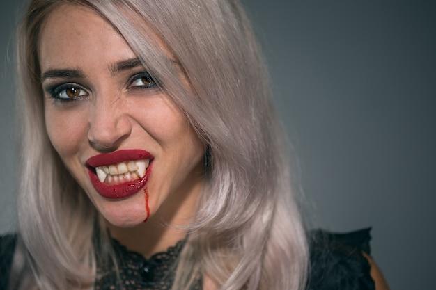 Retrato de una mujer vampiro con la boca ensangrentada y los dientes colmillos celebrando una fiesta diabólica feliz halloween