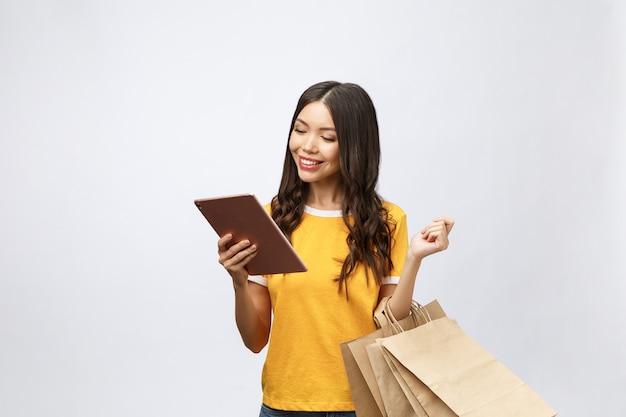 Retrato de mujer en vestido de verano sosteniendo bolsas de paquetes con compras después de compras en línea