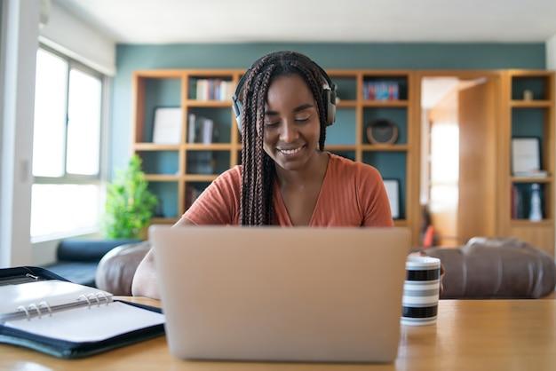 Retrato de una mujer en una videollamada con una computadora portátil y auriculares mientras trabaja desde el concepto de hogar