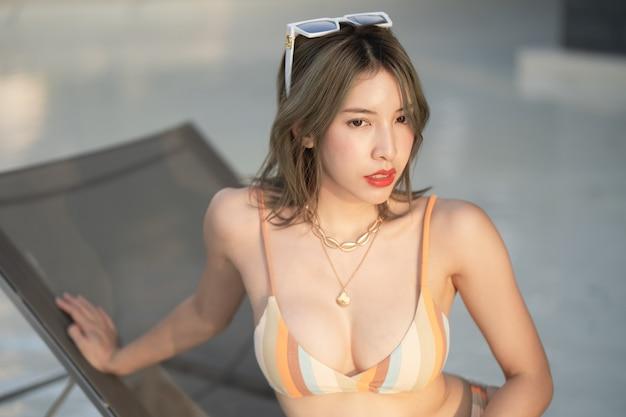 Retrato de mujer vistiendo bikini tumbado tomando el sol en la tumbona cerca de la piscina