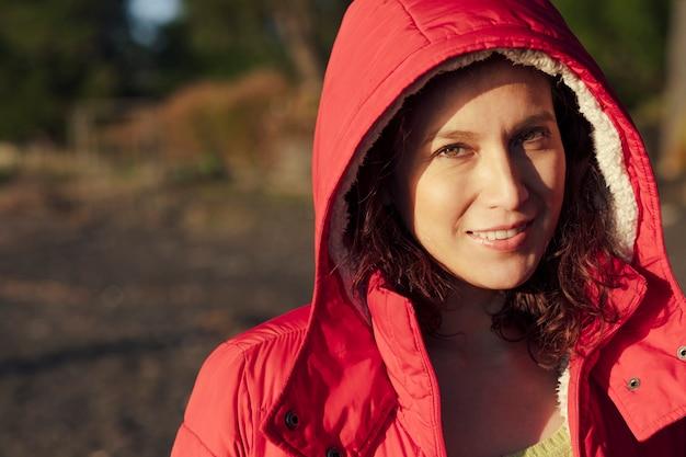 Retrato mujer vistiendo un impermeable rojo mirando a la cámara y sonriendo