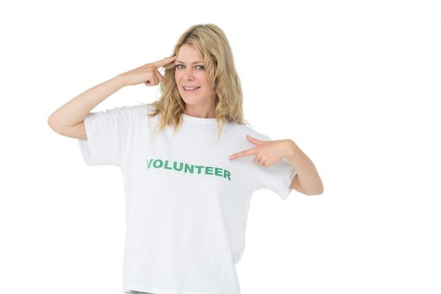 Retrato de una mujer voluntaria feliz apuntando a sí misma