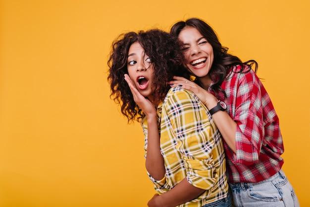 Retrato de mujeres americanas de buen humor. chica en rojo se ríe emocionalmente, bromeó novia sorprendida en camisa amarilla.