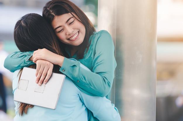 Retrato de mujeres asiáticas felices que abrazan a cada fondo al aire libre de la ciudad del amigo