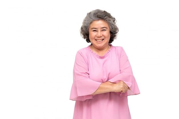 Retrato de mujeres asiáticas mayores con los brazos cruzados y una sonrisa aislada sobre la pared blanca, madura sonriendo y mirando a cámara, concepto de sentimiento feliz