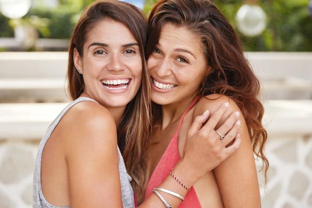 Retrato de mujeres de aspecto agradable que tienen cabello oscuro, piel sana y sonrisas agradables, se abrazan, felices de conocerse después de mucho tiempo