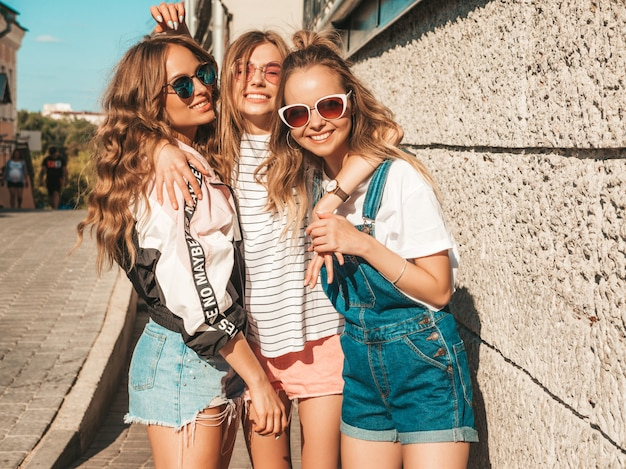 Retrato de mujeres despreocupadas sexy posando en la calle cerca de la pared. modelos positivos divirtiéndose en gafas de sol.