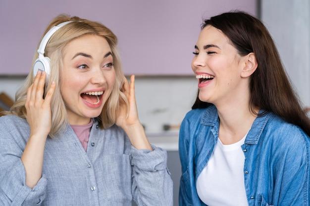 Retrato de mujeres felices riendo y escuchando música con auriculares