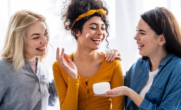 Retrato de mujeres felices riendo y jugando con crema hidratante