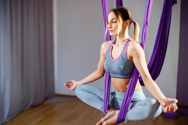 Retrato de mujeres jóvenes haciendo ejercicios de yoga antigravedad. entrenamiento de entrenador aerostático aerodinámico aéreo