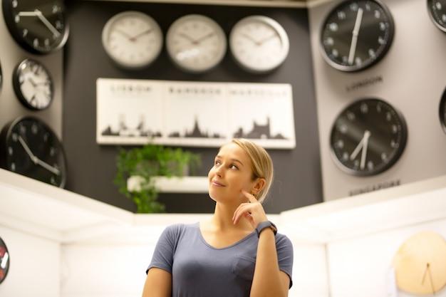 Retrato de mujeres mirando a otro lado mientras está de pie contra los relojes en la pared