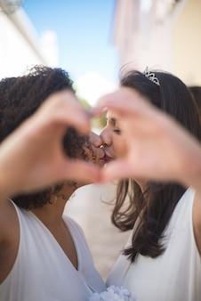 Retrato de mujeres recién casadas haciendo el signo del corazón
