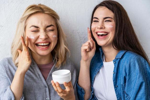Retrato de mujeres riendo y jugando con crema hidratante