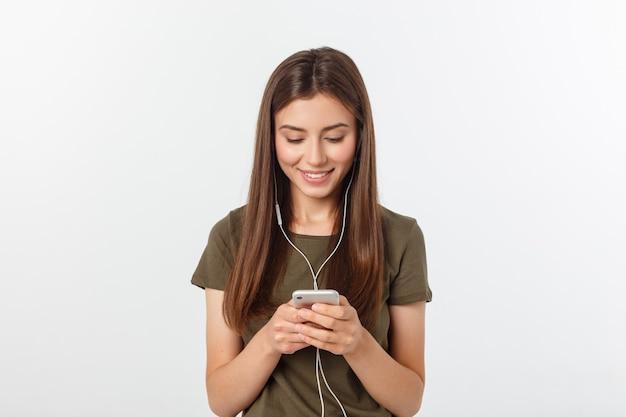 Retrato de una música que escucha alegre linda de la mujer en auriculares y baile aislado en un blanco.