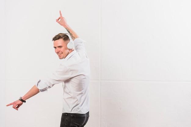 Retrato de una música que escucha feliz del hombre joven en el baile del auricular contra la pared blanca