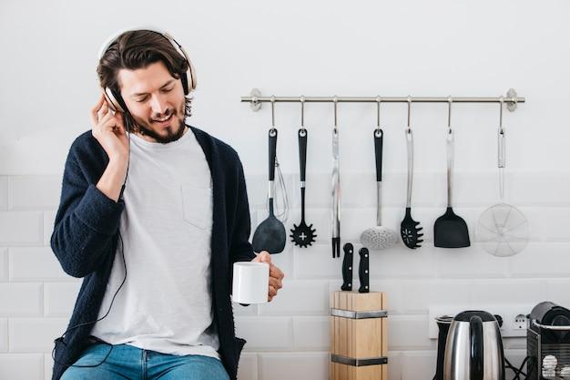 Retrato de una música que escucha del hombre en el auricular que se sienta en el contador de la cocina