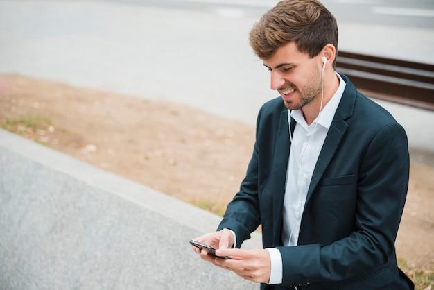 Retrato de una música que escucha del hombre de negocios en el auricular asociado en el teléfono móvil