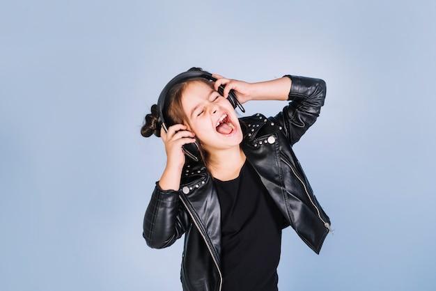 Retrato de una música que escucha de la muchacha en el auricular que ríe contra fondo azul