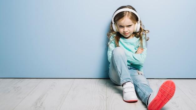 Retrato de una música que escucha de la muchacha enojada en el auricular que mira la cámara