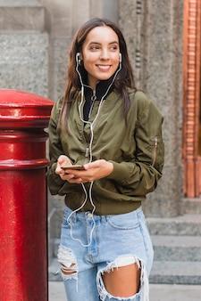 Retrato de una música que escucha de la mujer joven en el auricular a través del teléfono móvil