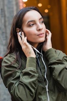 Retrato de una música que escucha de la mujer joven en el auricular