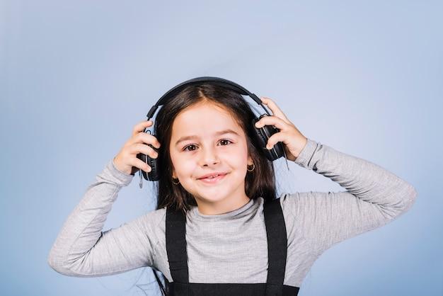 Retrato de una música que escucha sonriente de la muchacha en el auricular contra el contexto azul