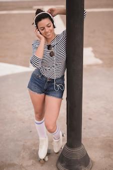 Retrato de una música que escucha sonriente de la mujer joven en el auricular que se coloca cerca del pilar
