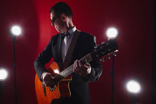 Retrato de músico clásico con guitarra en estudio rojo con iluminación escénica. guitarrista con gafas negras y traje con pajarita improvisa en el instrumento