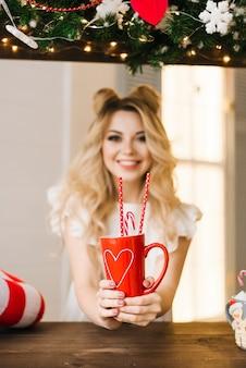 Retrato de navidad de una hermosa niña con una taza roja en un bar de navidad. año nuevo y concepto de navidad. enfoque selectivo