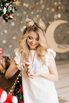 Retrato de navidad de una hermosa niña con una taza roja en un bar de navidad. año nuevo y concepto navideño