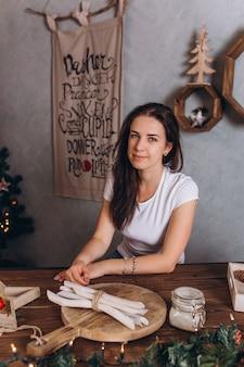 Retrato de navidad de joven mujer bonita morena en casa acogedora