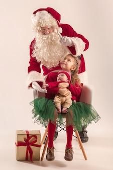 Retrato de navidad de linda niña recién nacida y bonita hermana adolescente vestida con ropa de navidad y hombre vestido con sombrero y traje de santa