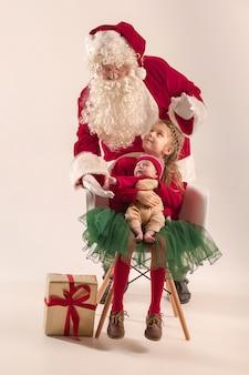 Retrato de navidad de linda niña recién nacida, bonita hermana adolescente, vestida con ropa de navidad y santa claus con caja de regalo
