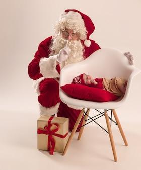 Retrato de navidad de linda niña recién nacida, vestida con ropa de navidad y hombre vestido con traje y sombrero de santa