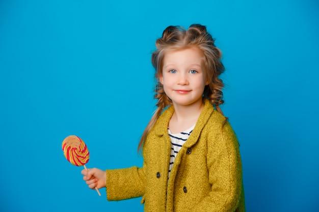 Retrato de una niña en un abrigo con una piruleta en un espacio azul coloreado