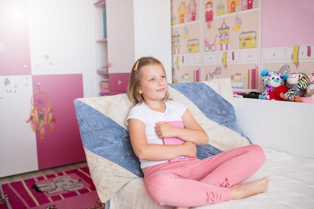 Retrato de niña adolescente caucásica soñando en su habitación sosteniendo el libro en las manos