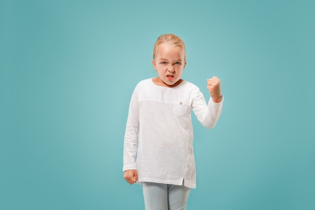Retrato de niña adolescente enojada en un estudio azul