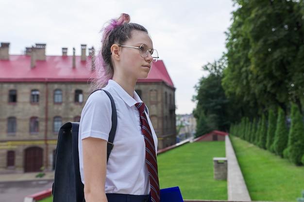 Retrato de niña adolescente con mochila para ir a la escuela, mañana de otoño de verano, fondo del edificio de la escuela. regreso a la escuela, regreso a la universidad