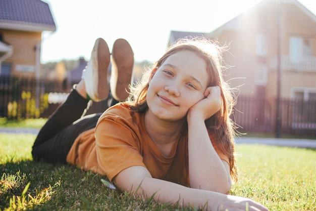 Retrato de niña adolescente sonriente tumbado en la soleada hierba verde del pueblo cabaña en el fondo