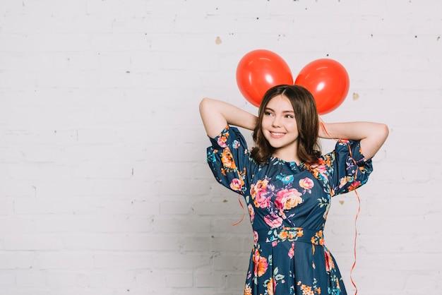 Retrato de niña adolescente sosteniendo globos rojos sobre su cabeza mirando lejos