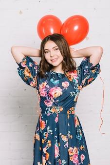 Retrato de niña adolescente sosteniendo globos rojos sobre su cabeza