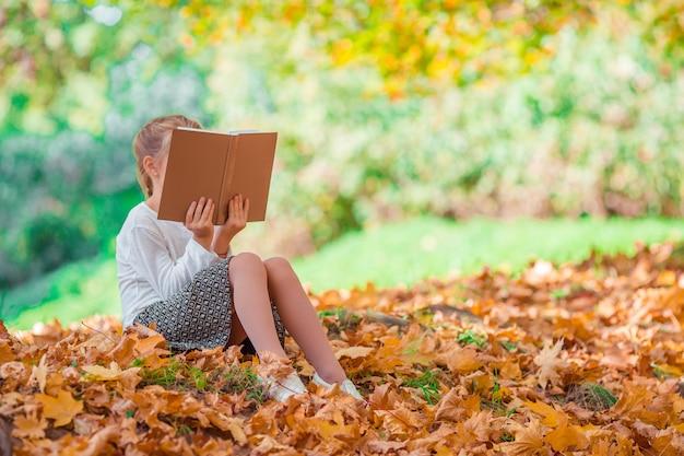 Retrato de niña adorable al aire libre en el hermoso día cálido con hoja amarilla en otoño