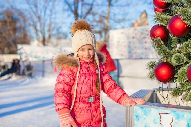 Retrato de niña adorable cerca de árbol de navidad en la pista de patinaje