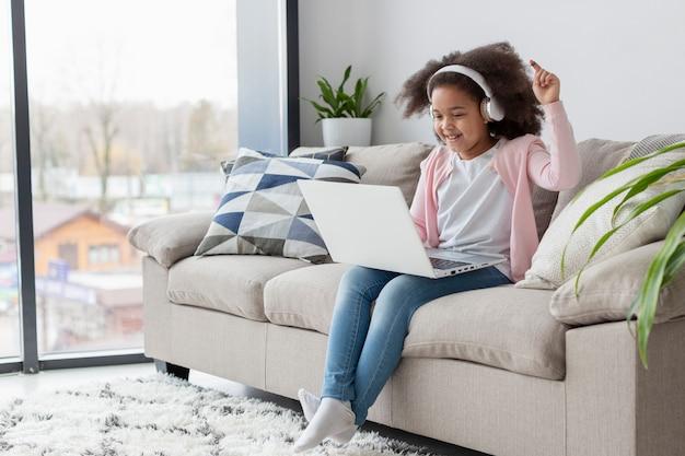 Retrato de niña adorable escuchando música en casa