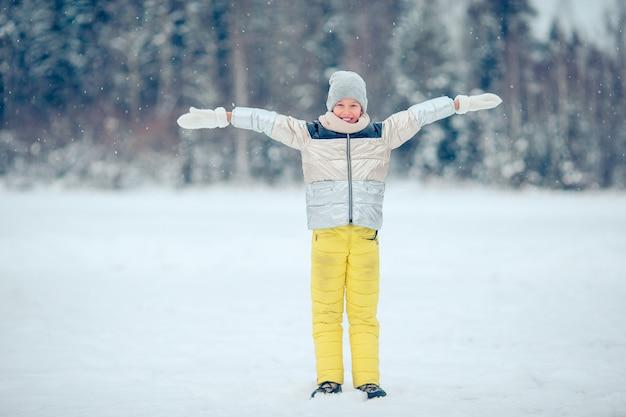 Retrato de niña adorable en nieve soleado día de invierno