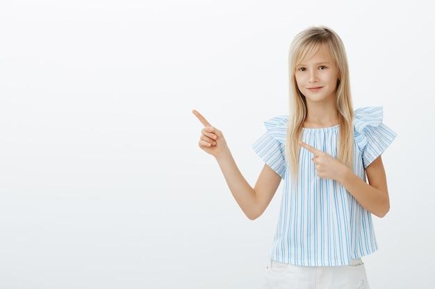 Retrato de niña adorable tranquila y complacida con cabello rubio, apuntando a la esquina superior izquierda y sonriendo amigablemente, pidiendo permiso para comprar helado sobre una pared gris