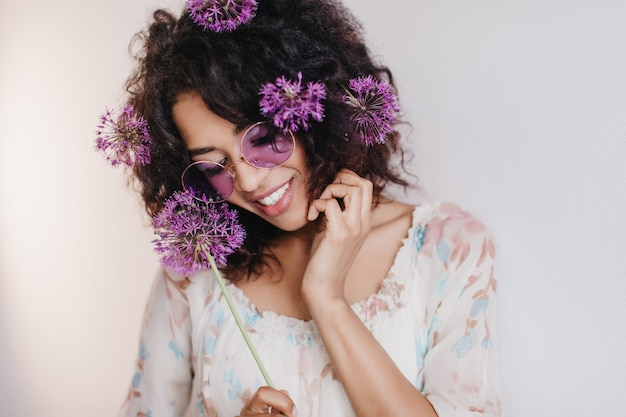 Retrato de niña africana agradable posando soñadora. mujer joven negra con flores de color púrpura en el pelo sonriendo durante la sesión de fotos.
