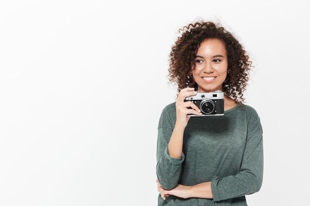 Retrato de una niña africana casual bastante alegre que se encuentran aisladas sobre la pared blanca, sosteniendo la cámara de fotos