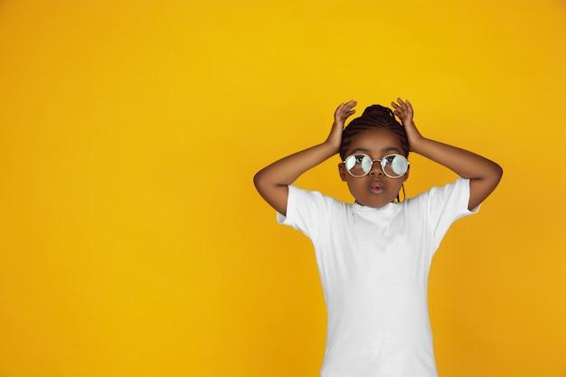 Retrato de niña afroamericana aislado en estudio amarillo