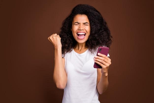 El retrato de una niña afroamericana encantada usa un teléfono inteligente, lee las noticias de las redes sociales, celebra la victoria, levanta los puños y usa una camiseta blanca.